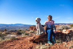 Happy senior woman on an outdoor hike with her dog. Enjoying nature on a sunny day. Enjoying a scenic overlook in St. George, Utah