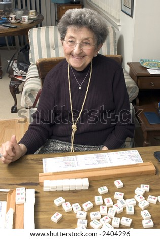happy senior woman playing mah-jong with friends