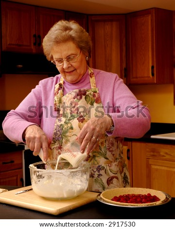 Happy senior woman pouring  milk into no-cook cherry pie filling. - stock photo