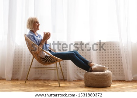 Happy senior woman relaxing on chair near window and drinking tea, side view, copy space