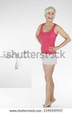 Happy senior woman showing weight loss