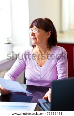Happy senior woman sitting at the table and calculating her finances at home near the computer looking at the window