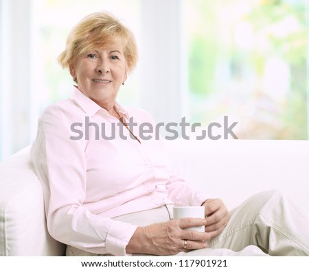 Happy senior woman sitting on a couch while she is drinking a cup of coffee
