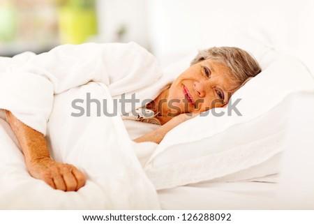 happy senior woman sleeping on bed