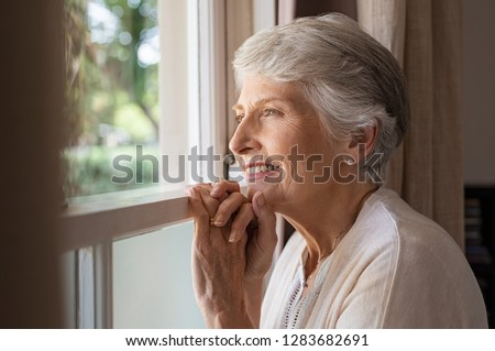 Happy senior woman standing at window and looking outside. Beautiful grandmother smiling while looking through the window. Cheerful old woman relaxing in home while standing at window sill.