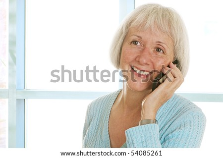 Happy senior woman talking on her cell phone. The image has a slightly soft, glowing look that is by design.