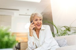 Happy senior woman using mobile phone at home. Smiling cool old woman with white hair sitting on sofa and messaging with smartphone. Beautiful stylish elderly lady talking on cellphone.
