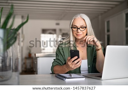 Photo of Happy senior woman using mobile phone while working at home with laptop. Smiling cool old woman wearing eyeglasses messaging with smartphone. Beautiful stylish elderly lady browsing site on cellphone.