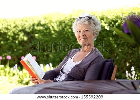 Happy senior woman with book in hand sitting in her backyard looking at camera smiling - Elder woman reading novel in garden