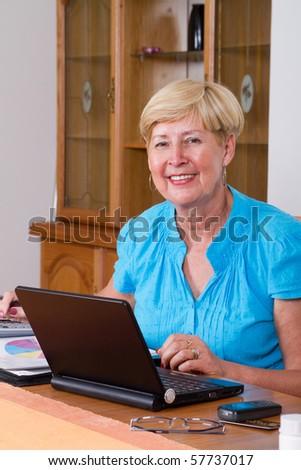 happy senior woman working on home finance