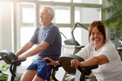 Happy senior woman working out in gym. Smiling elderly couple exercising in gym on stationary bicycle, focus on woman.