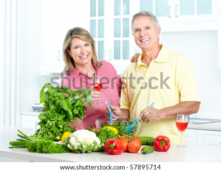 Happy seniors couple cooking at kitchen