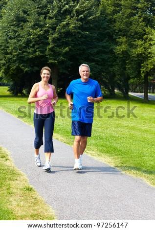 Happy seniors couple jogging in the park.