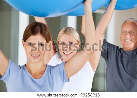 Happy seniors doing rehab exercises with gym balls in fitness center