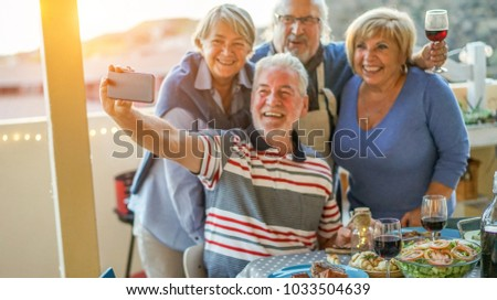 Happy seniors friends taking a selfie photo with smartphone camera at barbecue dinner in house terrace - Mature people having fun with new trend technology - Focus on mobile cell phone