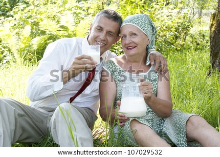 Happy seniors mother treats the son of the businessman with pair milk in a summer garden