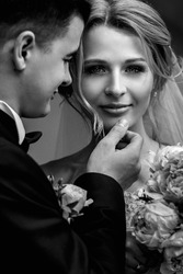 Happy sensual handsome groom and blonde beautiful bride in white dress hugging  b&w