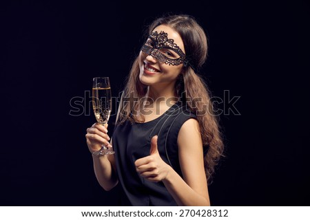 Happy sensual woman wearing party mask, holding a glass with champagne over dark background and showing thumb up gesture.