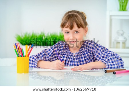 Shutterstock Happy seven year old girl drawing at home. Free time, activity and hobby. Education.