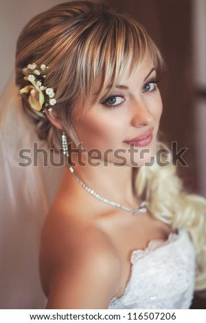 Happy sexy beautiful bride blond girl in white wedding dress with hairstyle and bright makeup waiting for groom. Romantic lady in bridal dress and flowers in hair have final preparation for wedding