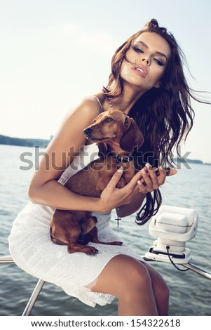 happy sexy woman with dog on the luxury boat in open sea in summer. Caucasian female model. Outdoors, lifestyle.