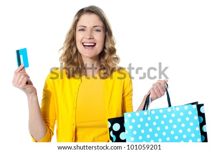 Happy shopaholic female laughing. Holding credit-card and shopping bags