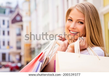Happy shopaholic girl. Beautiful young cheerful woman holding shopping bags and looking at camera while standing outdoors - stock photo