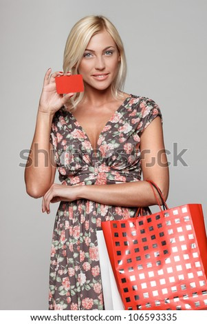 Happy shopping female holding blank credit card