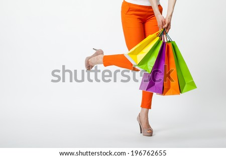 Happy shopping! Unrecognizable woman in orange pants holding multicolored shopping bags