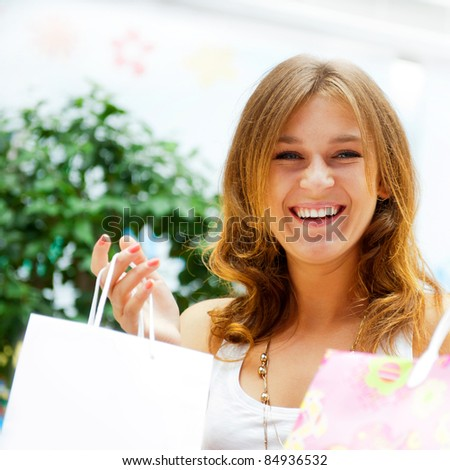 Happy shopping woman at the mall preparing gifts for her friends and relatives on christmas and boxing day. She is smiling and full of energy. Blank balloon with copyspace for your needs