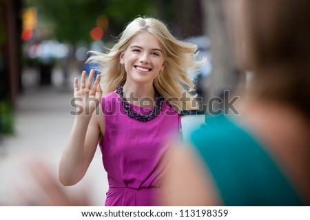 Happy shopping woman greeting friend on street