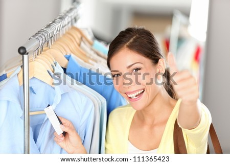 Happy shopping woman showing thumbs up while holding price tag on clothes on clothing rack. Beautiful joyful smiling multiethnic Asian Chinese / Caucasian young female shopper.