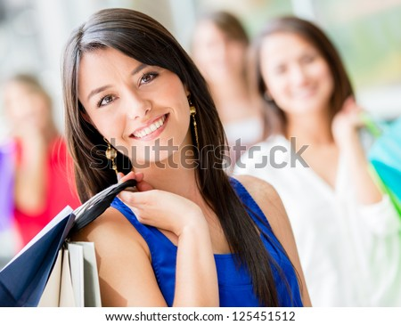 Happy shopping woman with a group of friends at the background - stock photo