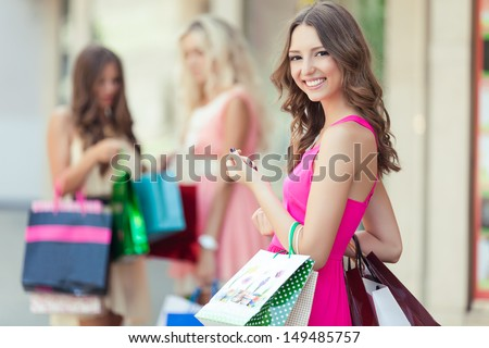Happy Shopping Woman With A Group Of Friends At The Background