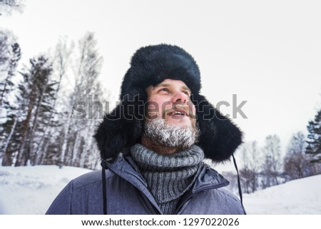 Happy Siberian Russian man with a beard smiles and lets out steam from his mouth in hoarfrost in freezing cold in the winter freezes in a village in a snowdrift and wears a hat with a earflap. #1297022026