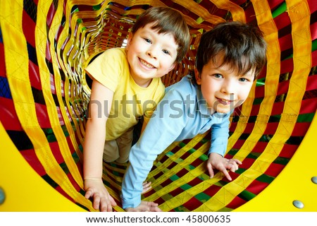 Happy siblings looking at camera while having fun inside toy tunnel