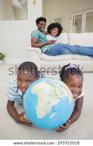 Happy siblings lying on the floor holding globe at home in the living room