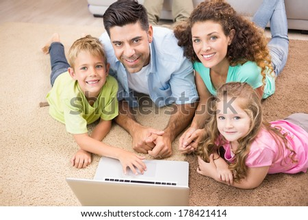 Happy siblings lying on the rug using laptop with their parents at home in living room