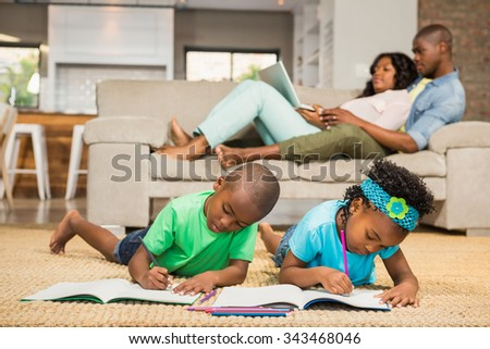 Happy siblings on the floor drawing in the living room #343468046