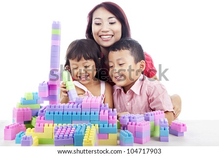 Happy siblings playing block with mother at home isolated on white