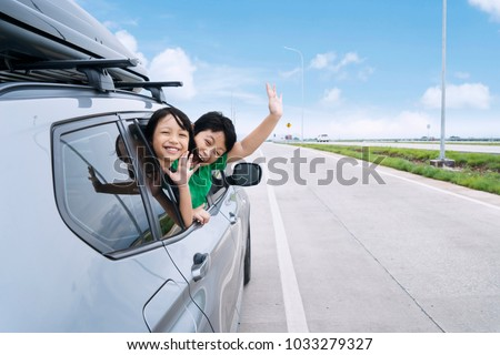 Happy siblings waving hands travel by car against blue sky. Summer road trip concept #1033279327