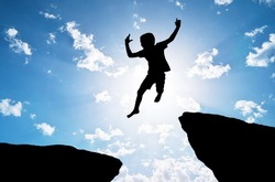 Happy silhouette of boy jumps over a cliff. Emotional and coceptual scene.