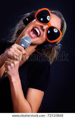 Happy singing woman with headphones  and microphone. Karaoke
