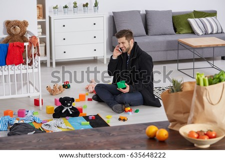Happy single father sitting on a floor with children toys in studio apartment #635648222