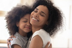 Happy single foster mother embracing cute little adopted daughter head shot close up image. Smiling loving family of two bonding, hugging, cuddling, having fun together. Positive tender family moment.