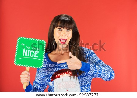 Happy single woman in ugly knitted sweater pointing to nice sign over red background