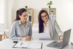 Happy single young business woman consulting bank manager, financial advisor or loan broker. Smiling estate agent meeting client at office, talking, showing and offering house design options on laptop
