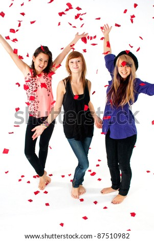 Happy sisters with petals of rose falling