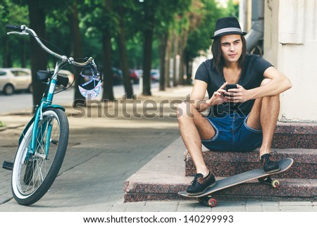 Happy skateboarder sitting on stairs. Young active people. Outdoors