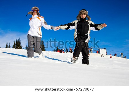 happy skiers hurry on snow
